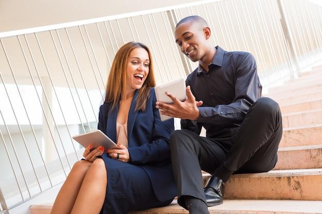 Uomo sorridente che mostra lo schermo femminile della compressa del collega sulle scale Foto Gratuite