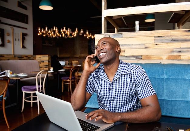 Uomo sorridente che parla sul telefono cellulare mentre sedendosi al caffè con il computer portatile Foto Premium