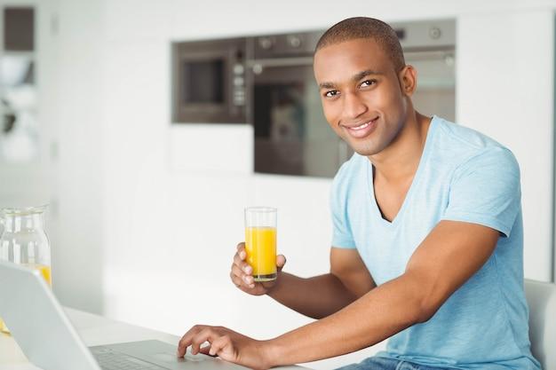 Uomo sorridente che per mezzo del computer portatile e bevendo succo d'arancia in cucina Foto Premium
