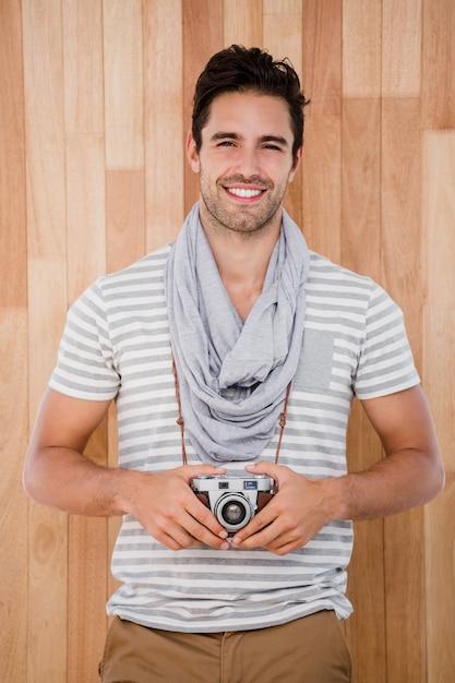 Uomo sorridente che sta con una macchina fotografica Foto Premium