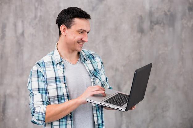 Uomo sorridente che sta e che per mezzo del computer portatile Foto Gratuite