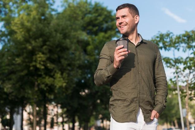 Uomo sorridente che sta nel parco che tiene la tazza di caffè eliminabile Foto Gratuite