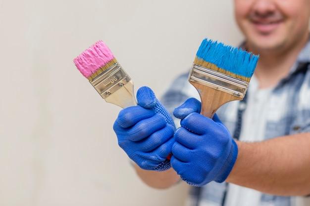 Uomo sorridente che tiene il pennello rosa e blu Foto Gratuite