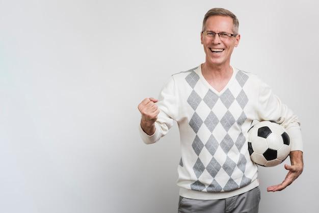Uomo sorridente che tiene un pallone da calcio con copia-spazio Foto Gratuite