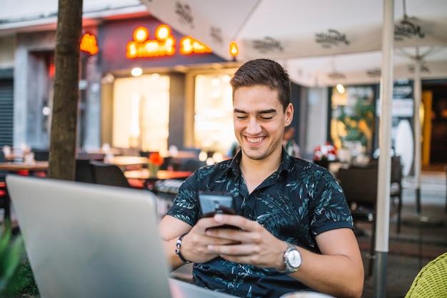 Uomo sorridente che utilizza telefono cellulare nel caf� Foto Gratuite