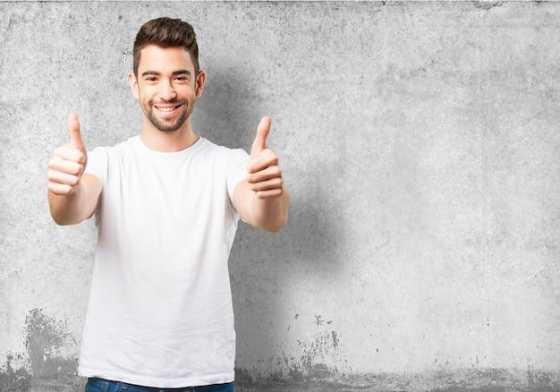 Uomo sorridente con il pollice in alto Foto Gratuite