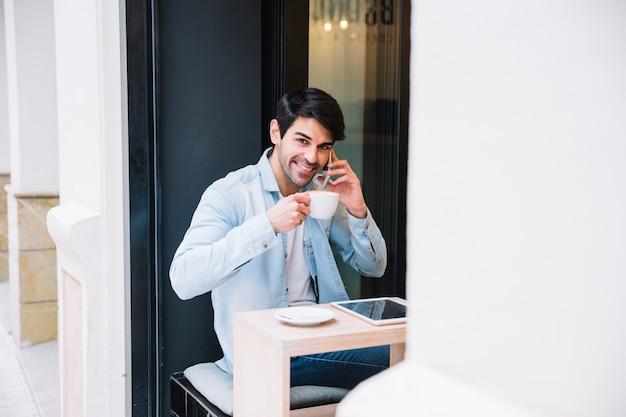 Uomo sorridente con la tazza che parla sullo smartphone Foto Gratuite