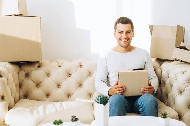 Uomo sorridente con scatola di cartone Foto Gratuite