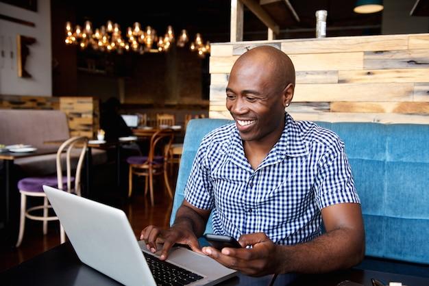 Uomo sorridente con un telefono cellulare che si siede al caffè usando il portatile Foto Premium