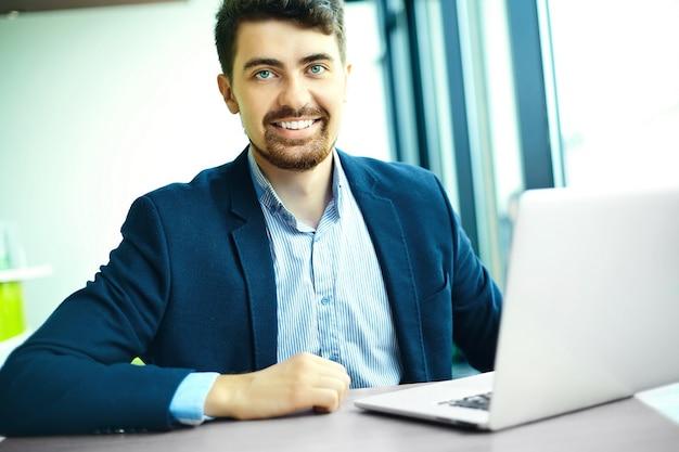 Uomo sorridente dei pantaloni a vita bassa di giovane modo nel caffè della città durante l'ora di pranzo con il taccuino in vestito Foto Gratuite