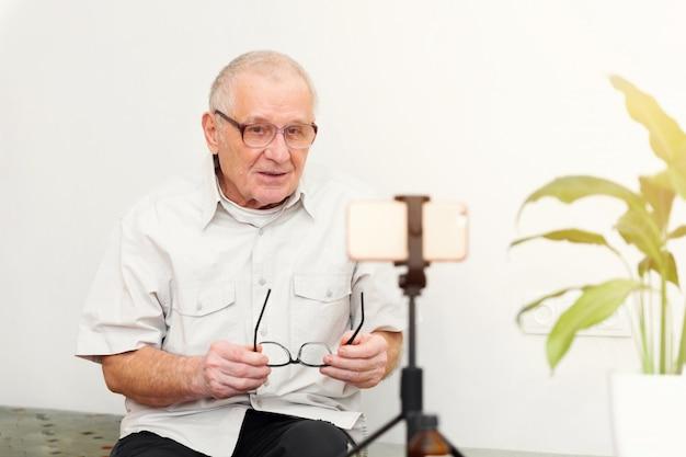 Uomo sorridente di eldery che esamina macchina fotografica che fa il video blog o chiamata a casa che si siede sul sofà che risale ritratto in linea di colpo in testa Foto Premium