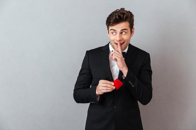 Uomo sorridente in scatola ufficiale della tenuta del vestito con l'anello di proposta Foto Gratuite