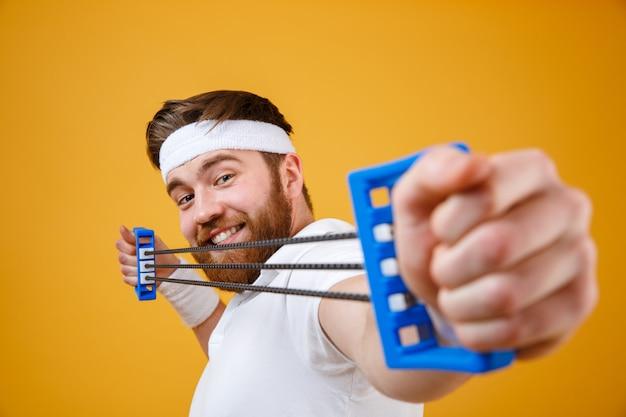 Uomo sportivo di forte ragazzo atletico che allunga espansore sull'arancia Foto Gratuite