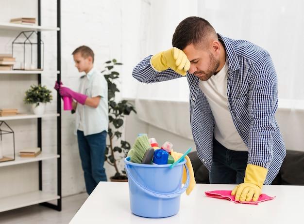 Uomo stanco dopo aver pulito la casa Foto Gratuite