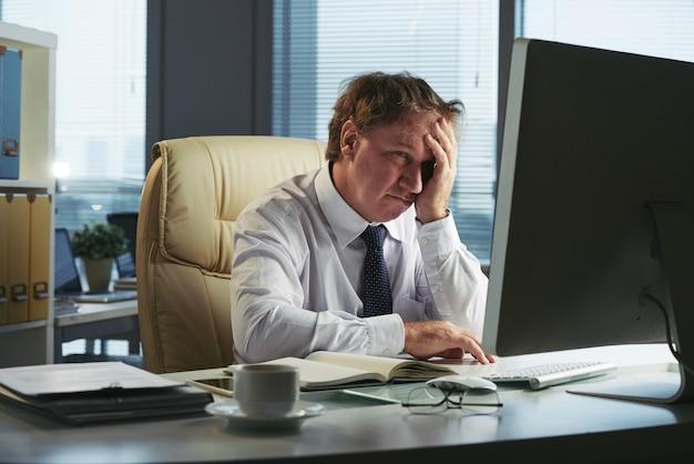 Uomo stressato con mal di testa lavorando al mattino presto nel suo ufficio Foto Gratuite