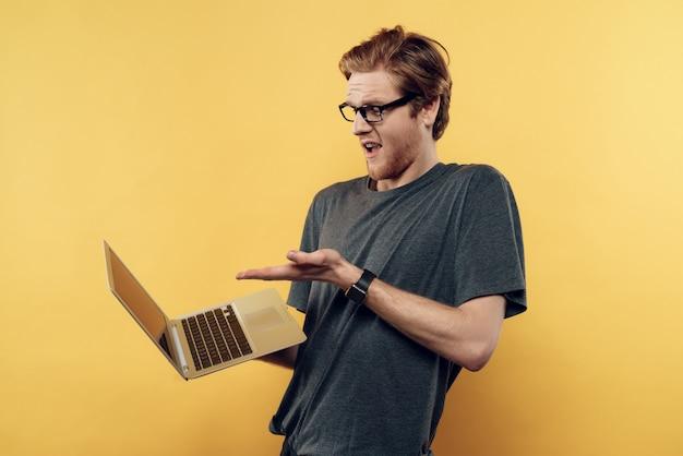 Uomo stupito in bicchieri guardando lo schermo del laptop Foto Premium