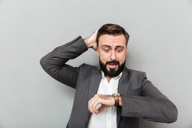Uomo stupito orizzontale che esamina orologio, toccando la sua testa che posa tardi isolata sopra grey Foto Gratuite