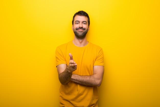 Uomo su colore giallo vibrante isolato che agita le mani per la chiusura di un buon affare Foto Premium