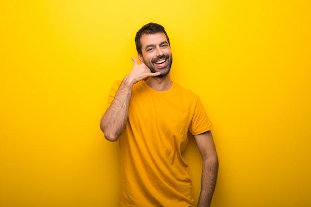 Uomo su colore giallo vibrante isolato che fa gesto del telefono. chiamami segno Foto Premium