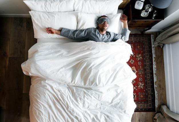 Uomo sul letto che dorme con una copertura per gli occhi Foto Premium