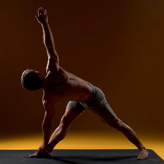 Uomo sulla stuoia di yoga che fa esercizio Foto Gratuite