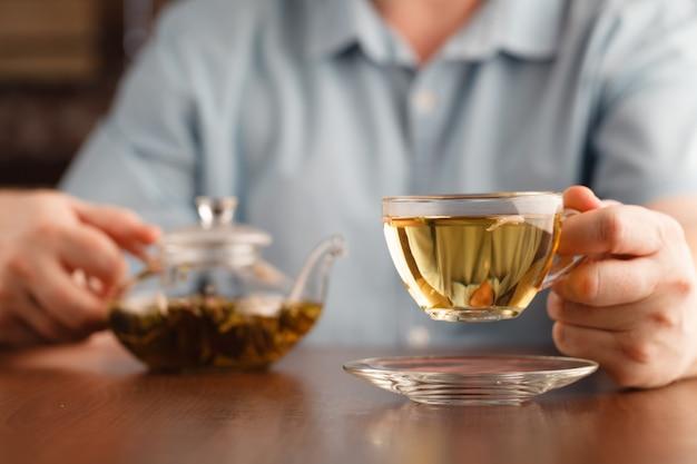 Uomo tenere la tazza in mano e offrire il tè Foto Premium