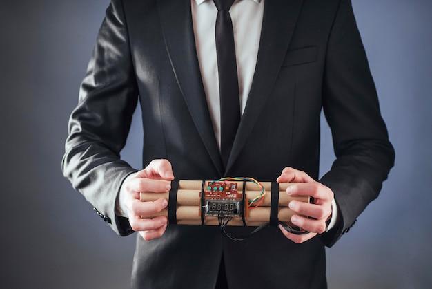 Uomo terrorista in un abito nero con esplosivi Foto Premium