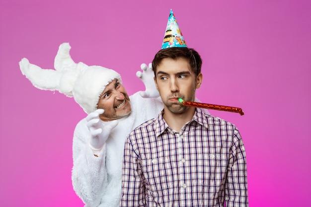 Uomo ubriaco spaventoso del coniglio sopra la parete viola. festa di compleanno. Foto Gratuite