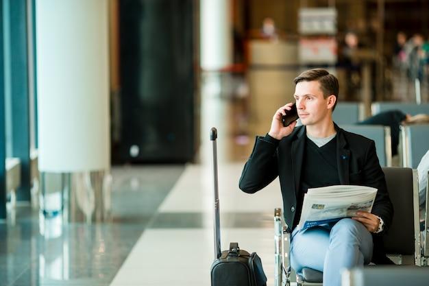 Uomo urbano di affari che parla sullo smart phone dentro in aeroporto. Foto Premium