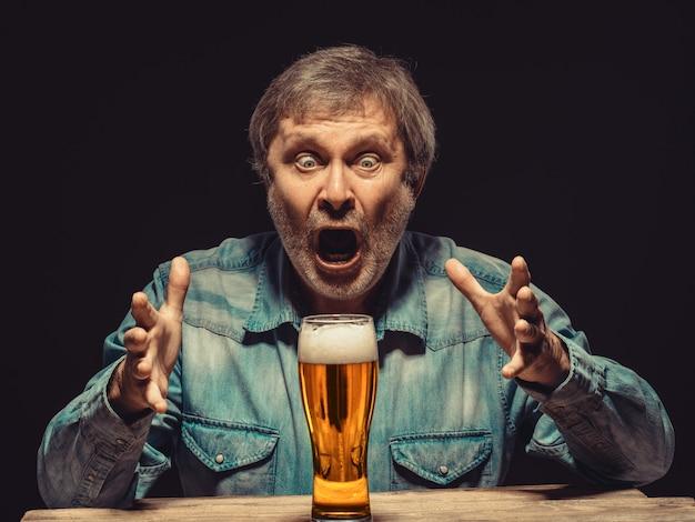 Uomo urlando in camicia di jeans con un bicchiere di birra Foto Gratuite