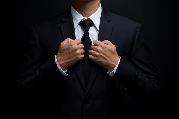 Uomo vestito di nero e aggiustandosi la cravatta Foto Premium