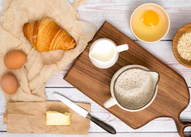 Uova; croissant; burro; latte; crusca di farina e avena sulla scrivania in legno Foto Gratuite