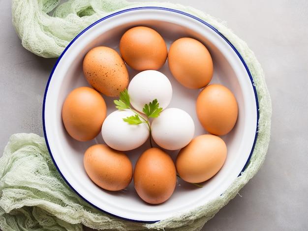 Uova di gallina bianche e marroni in ciotola Foto Premium