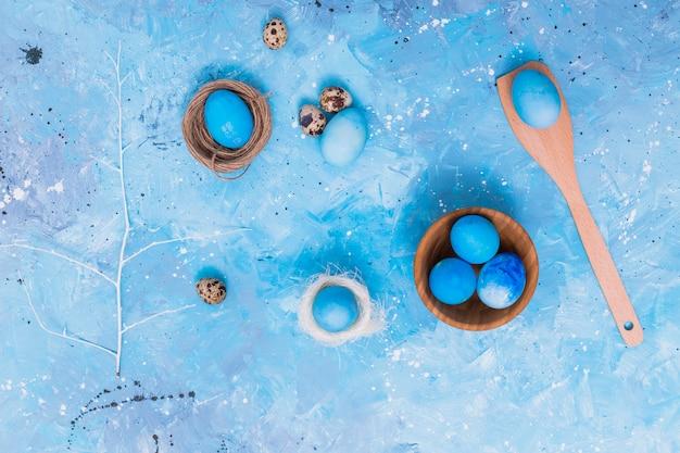 Uova di pasqua blu in nidi sul tavolo Foto Gratuite