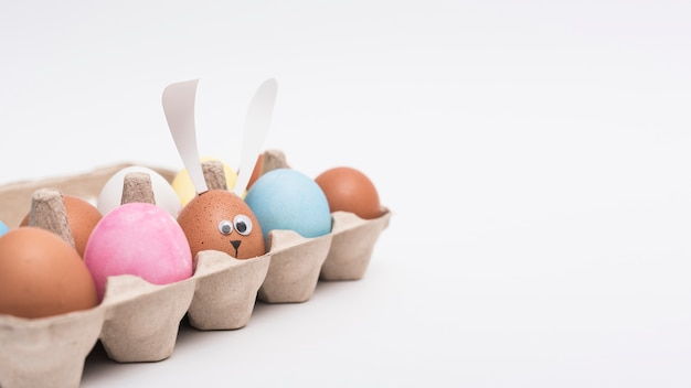 Uova di pasqua colorate in rack sul tavolo Foto Gratuite