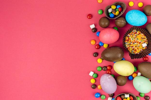 Uova di pasqua con uova di cioccolato e caramelle sul tavolo Foto Gratuite