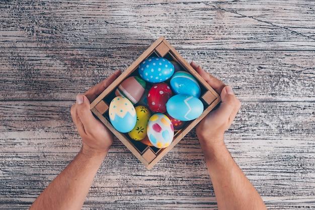 Uova di pasqua distese in scatola di legno con le mani di man_s su fondo di legno. Foto Gratuite