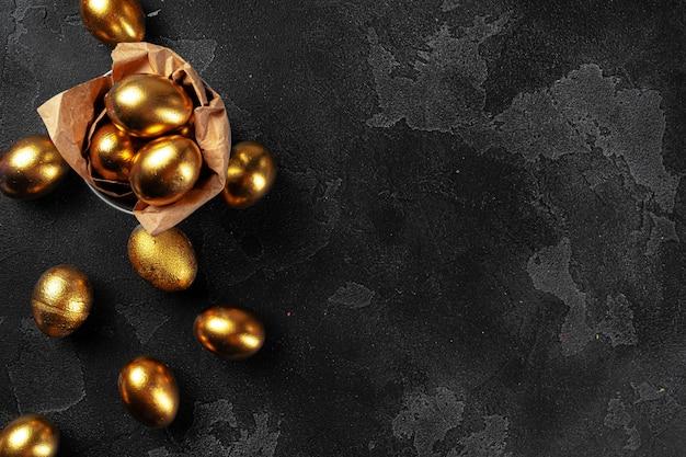 Uova di pasqua dorate su una priorità bassa concreta nera Foto Premium