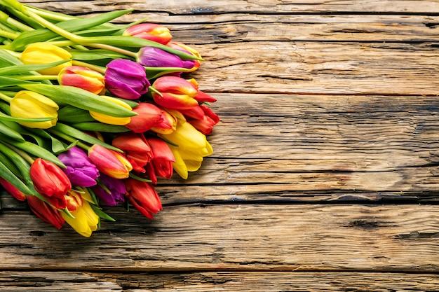 Uova di pasqua e tulipani sulle plance di legno Foto Premium