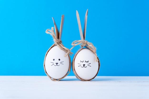 Uova di pasqua fatte in casa con facce e orecchie di coniglio su sfondo blu. concetto di pasqua Foto Premium