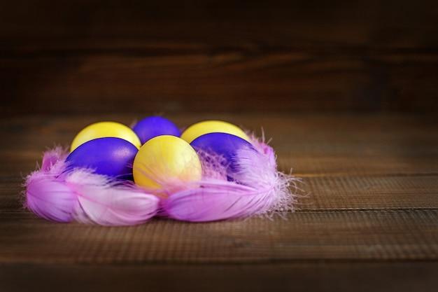Uova di pasqua gialle e viola nel nido. concetto e buone vacanze di pasqua. Foto Premium