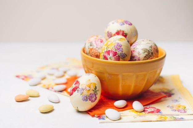 Uova di pasqua in ciotola vicino a tovaglioli e piccole pietre Foto Gratuite