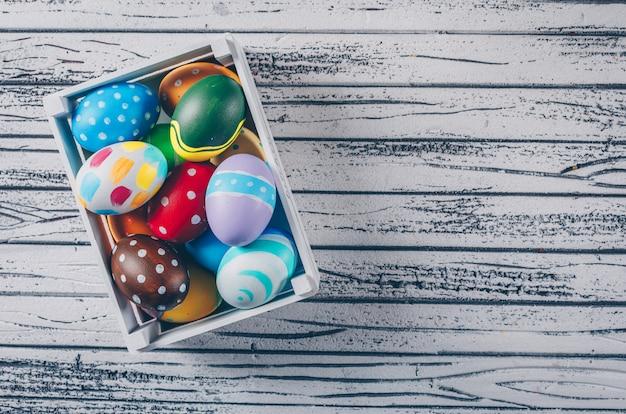 Uova di pasqua in scatola di legno su fondo di legno leggero. Foto Gratuite