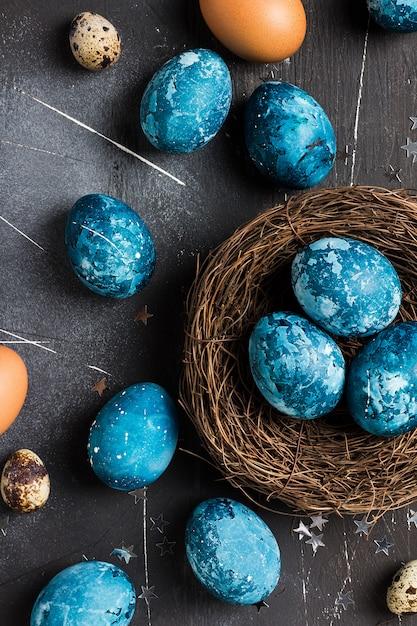 Uova di pasqua nel nido dipinto a mano in blu Foto Gratuite