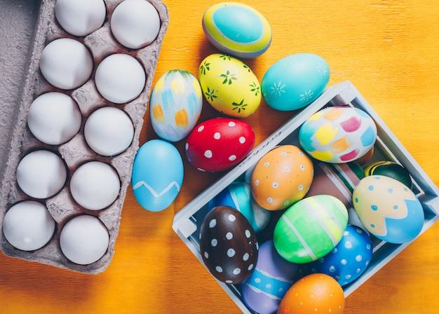 Uova di pasqua nella vista superiore del cartone dell'uovo e della scatola di legno su fondo di legno giallo Foto Gratuite