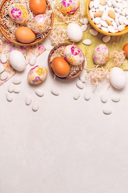 Uova di pasqua sui piatti e piccole pietre in ciotola sui tovaglioli Foto Gratuite