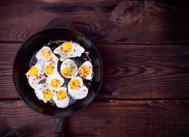 Uova di quaglia fritte in una padella nera in ghisa Foto Premium