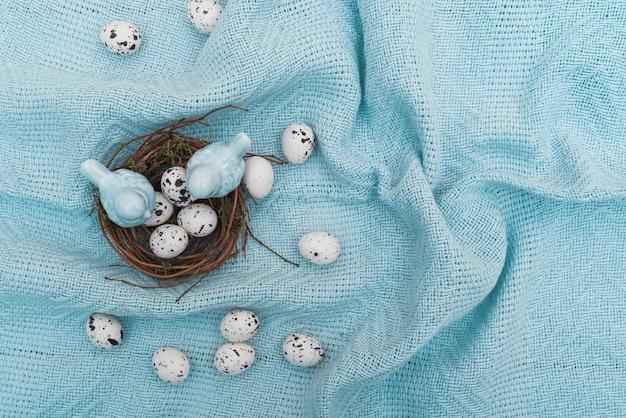 Uova di quaglia nel nido sul panno blu Foto Gratuite