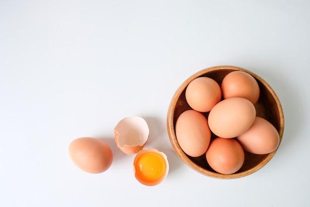 Uova fresche dall'azienda agricola disposte su un fondo di tavolo in legno bianco Foto Premium