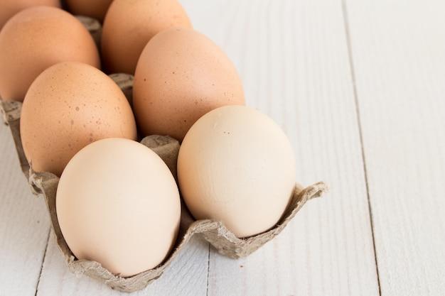 Uova fresche in pacchetto di cartone su legno bianco Foto Gratuite
